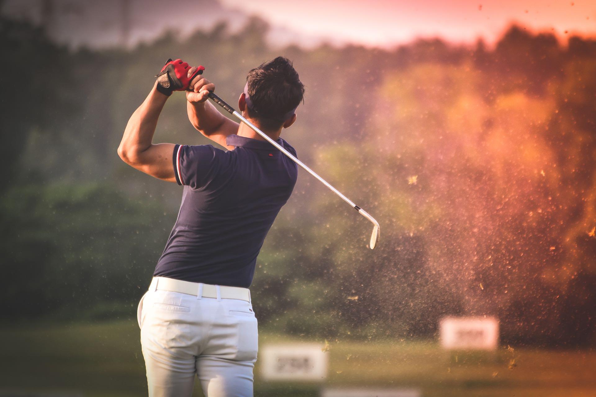Golfer hitting golf shot with club on course